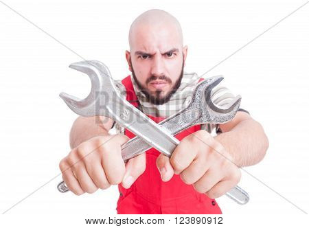 Angry mechanic or plumber holding crossed wrenches wearing red overall uniform isolated on white