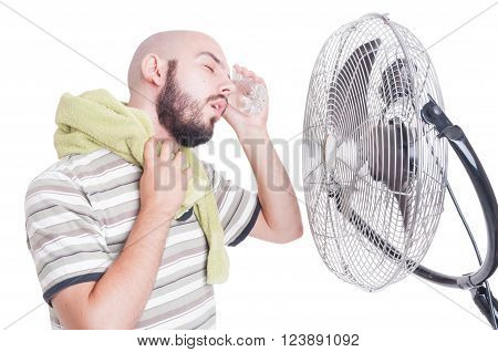 Man Cooling His Head With Cold Water Bottle And Fan