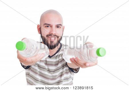 Smiling man offering or giving two bottles of cold water as hydration in summer heat concept