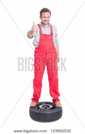 Smiling Mechanic Showing Like Standing On A Car Wheel