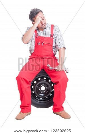 Tired Mechanic Sitting On Car Wheel And Having Headache