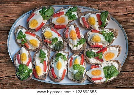 open-faced sandwiches plated with remoulade eggs fresh watercress and red peppers