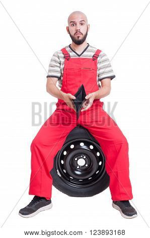 Broke mechanic showing his empty wallet isolated on white