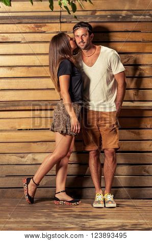 Happy couple in photo shooting outdoor on wooden background wearing autumn fall casual clothes