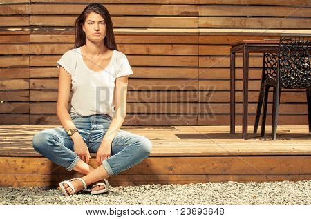 Gorgeous teen female model posing outdoor wearing jeans and t-shirt on wooden fence background