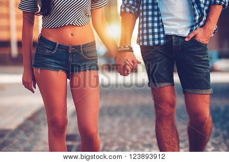 Always together. Close-up of beautiful young loving couple holding hands while walking along the street
