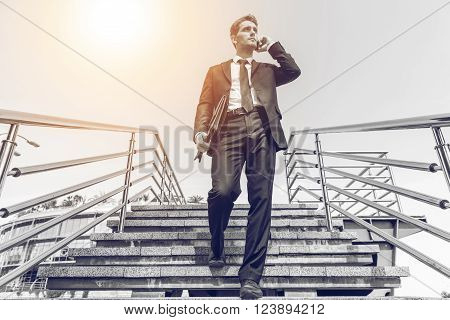 Confident businessman. Black and white image of confident young man in formalwear talking on the mobile phone while moving down by staircase