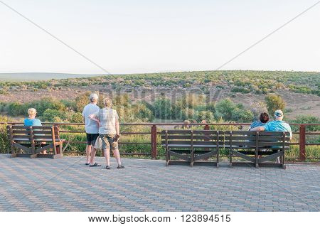 ADDO ELEPHANT NATIONAL PARK SOUTH AFRICA - FEBRUARY 23 2016: Unidentified tourists viewing buffalo in the late afternoon sun at the Nyati waterhole at the main camp