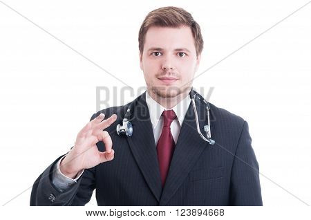 Elegant medic or doctor showing okay perfect gesture wearing suit and stethoscope isolated on white