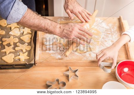 Father's and daughter's hands preparing cookies to bake. Kitchen scenery - happy family time.