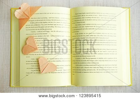 Book and heart shaped bookmarks on a light wooden background