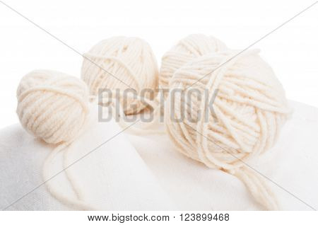 Balls of soft wool on cotton fabric isolated on white background