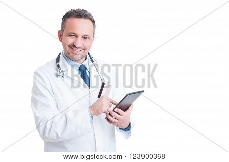 Smiling Doctor Or Medic Using Credit  Card And Wireless Tablet