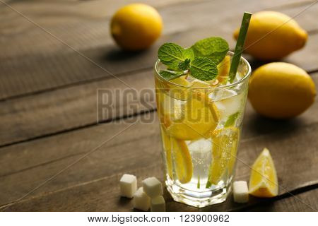 Lemonade with lemons, mint and sugar cubes on wooden table background