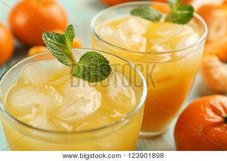 Fresh cocktails with ice, mint and tangerines on the wooden table, close up