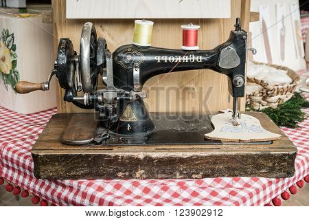 Trento Italy - December 15 2015: Old manual sewing machine used to embroider wooden shapes.