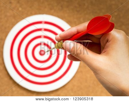 Selective focus of female hand holding red dart arrow point to target center of dartboard on cork background. Bullseye and Dart. target/goal business concept.