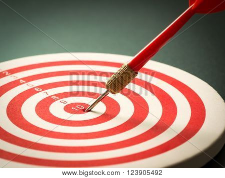 Selective focus of red dart arrow hitting target center of dartboard on black background. Bullseye and Dart. Success/fail business concept. Success hitting target aim goal achievement concept.
