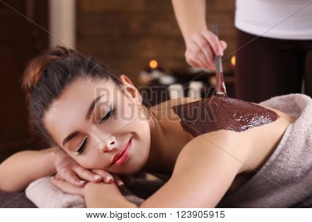 Beautiful young girl having cosmetic mask in spa salon