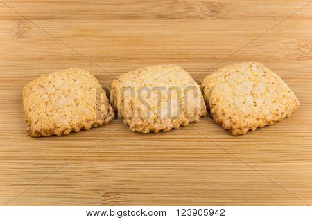 Three shortbread cookies on wooden bamboo table