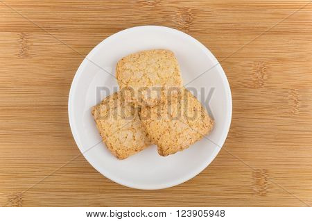 Three shortbread cookies in white saucer on wooden table