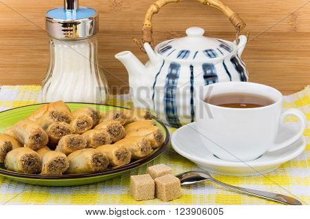 Baklava on plate sugar bowl and tea in cup on checkered tablecloth