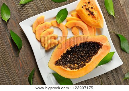 Halved papaya with slices on a white plate