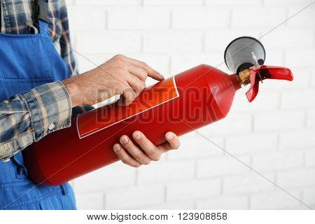 Man hands holding fire extinguisher on white brick wall background