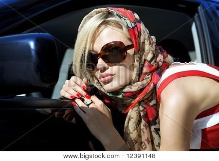 modern fashion blonde woman in dark sunglasses in the city
