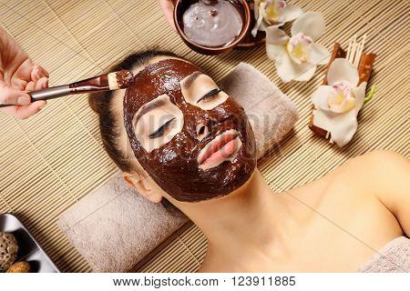 Beautiful young girl getting chocolate mask in spa salon