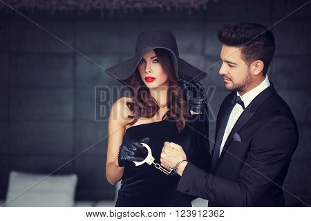 Sexy woman in hat holding macho man on handcuffs, bdsm