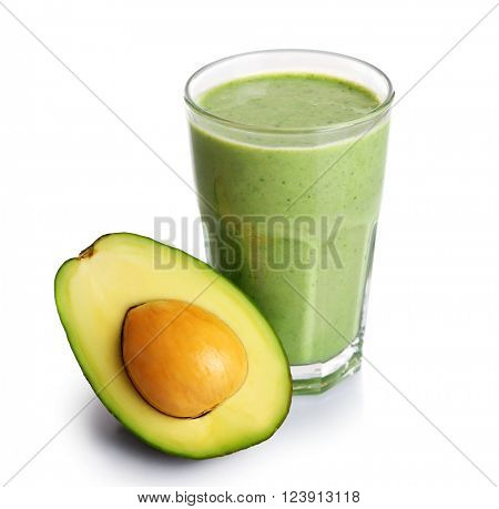 Glass of fresh avocado cocktail and avocado fruit isolated on white