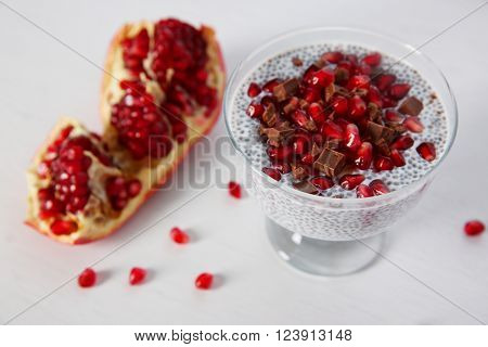 Chia seeds pudding with pomegranate grains and chocolate chips in glass saucer on white background