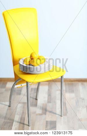 Plate of lemons on chair indoors