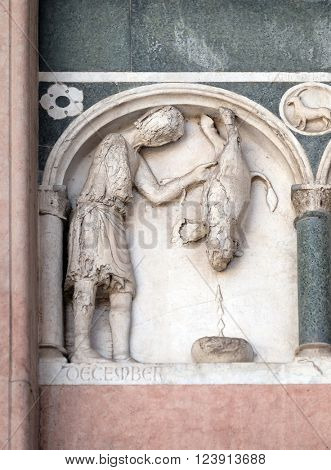LUCCA, ITALY - JUNE 06, 2015: December, detail of the bas-relief representing the Labor of the months of the year, portal of the Cathedral of St Martin in Lucca, Italy, on June 06, 2015