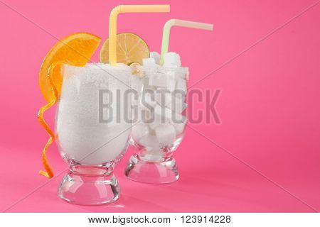 Glasses with lump, granulated sugar, cocktail straws and citrus slices on pink background