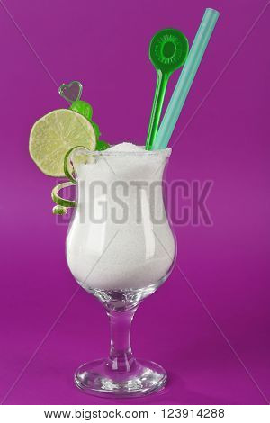Hurricane glass with granulated sugar, cocktail tube and lime slice on purple background