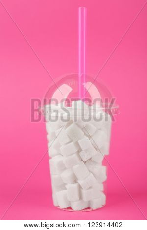 Plastic smoothie cup with lump sugar and cocktail tube on pink background