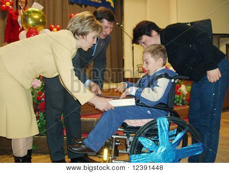 official persons donate the prize for disabled kid