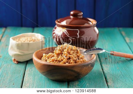 Wholegrain spelt porridge with butter in wooden bowl and raw spelt in linen bag on wooden table horizontal
