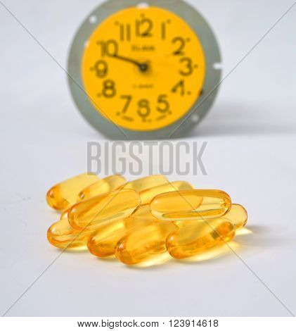 Picture Omega 3 pills in a fron of alarm clock