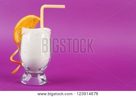 Glass with granulated sugar, cocktail straw and orange slice on purple background