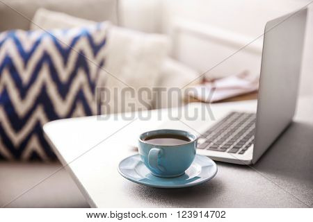 Modern interior. Comfortable workplace. Table with laptop and cup of coffee on it, close up
