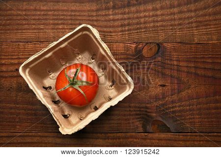 High angle view of a single tomato in a cardboard produce container on a dark wood surface.