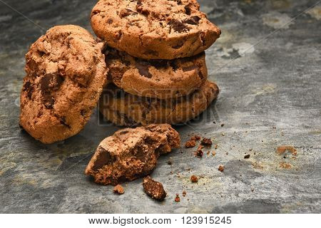 Closeup of a stack of chocolate chip cookies on a slate surface. Horizontal format with copy space.