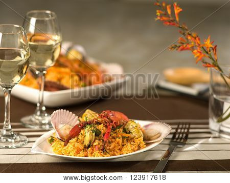 Seafood paella, arroz con mariscos, a typical Peruvian dish served with wine in a fine dining setting