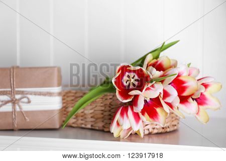 Bouquet of variegated tulips with gift box on white shelf