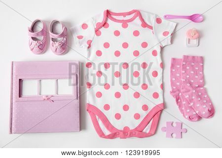 Baby clothes with photo album, spoon and nipple on white background