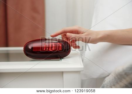 Female hand trying to stop digital clock ringing