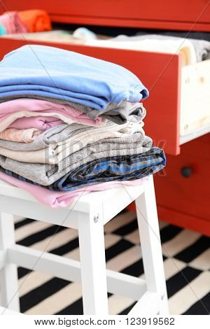 Stack of folded clothes on wooden stool closeup